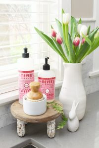 Dish soaps and scrub brush on a cake stand by the kitchen sink.